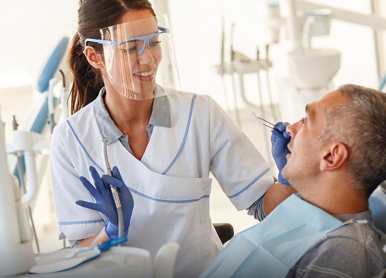Dentystka przeprowadzajaca przeglad napacjencie