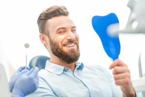 Usmiechniety mężczyzna sprawdzajacy swoje zeby w lustrze